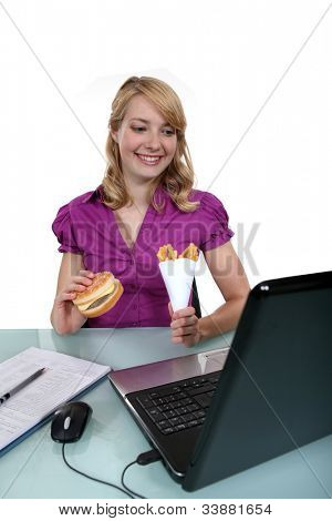 A businesswoman having junk food in her office.