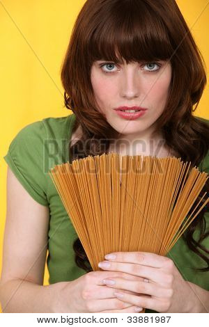 Woman holding uncooked spaghetti