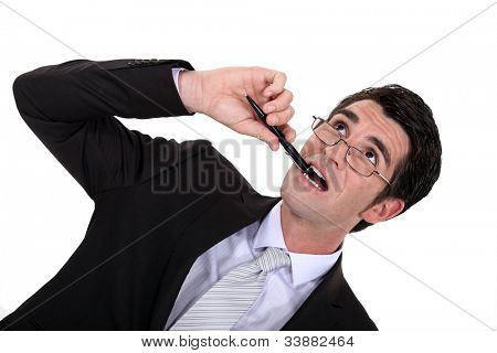 Businessman chewing his pen