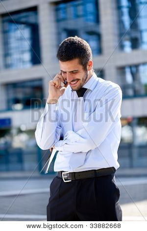 Young Caucasian businessman talking on smart phone outside modern office block