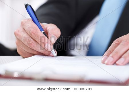 Businessman sitting at office desk signing a contract with focus on signature.