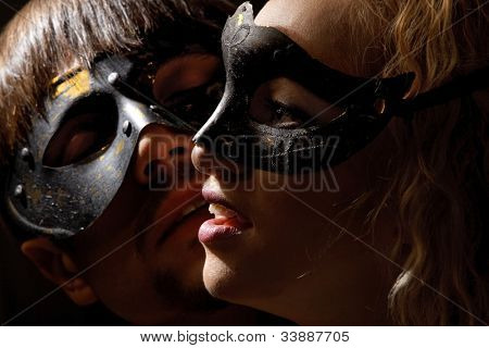 Portrait of young mysterious couple in a Venetian mask