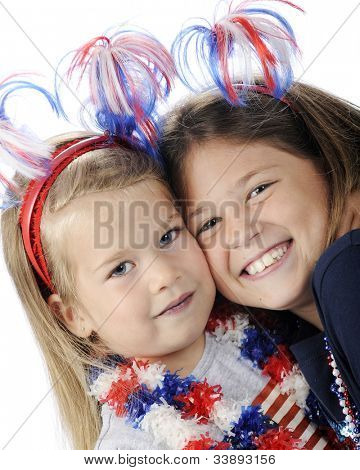 Closeup image of two sisters a decked out to celebrate America's Independence Day.  On a white background.