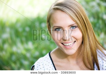 Beautiful young woman enjoying the Sun on the meadow with flowers on a warm summer day