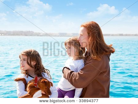 mother and daughter sister girls with dog on the sea sailing in a boat