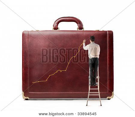 Young businessman on a ladder charting a positive trend graph on a suitcase