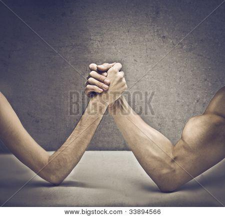 Closeup von einem muskulösen Mann spielt Armdrücken mit einem dünnen