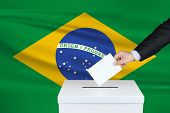 Election In Brazil. The Hand Of Man Putting His Vote In The Ballot Box. Waved Brazil Flag On Backgro poster
