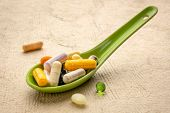 vitamins and supplements - pills and capsules and tablets on a Chinese ceramic spoon, healthcare, se poster