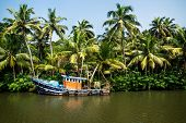 Old Ocean Fishing Boat Along The Canal Kerala Backwaters Shore With Palm Trees At A Sunny Day Betwee poster