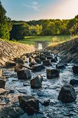 Vertical Shot - Strong Water Stream With Stones And Big Rocks Inside Flowing From Reservoir (dam) In poster