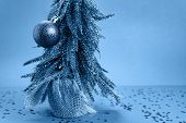 Christmas Tree With Toy Is On Blue Table With Stars On The Table And Blue Background Behind The Tree poster