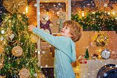 Cute Kid Decorating Christmas Tree With Bauble. Christmas Preparation Funny Little Boy Celebrating N poster