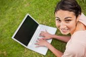 Woman looks towards her side while using a laptop as she lies prone in grass