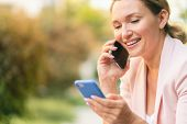 Close-up portrait of a smiling woman calling by phone on the street.  Happy businesswoman is using s poster