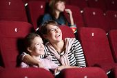 picture of cinema auditorium  - Loughing mother and daughter at the cinema watching a movie - JPG