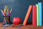 Composition of books, stationery and an apple on the teacher's desk in the background of the blackbo