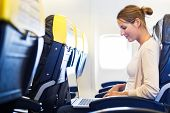 stock photo of intranet  - Young woman working on her laptop computer on board of an airplane during the flight - JPG