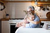 Cute Child Is Giving Gift Box To Grandmother. Kid Girl And Senior Woman Are Hugging In Cozy Kitchen  poster
