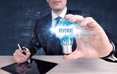 Businessman holding a light bulb with REVENUE inscription, new business concept poster