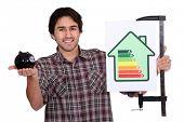 Постер, плакат: Человек держащий Копилка банка и энергетической эффективности логотип
