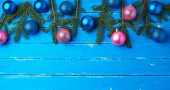 Green Spruce Branches, Pink And Dark Blue Shiny Christmas Balls On A Blue Wooden Background From Boa poster