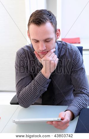 Man Concentrating As He Reads His Tablet Screen