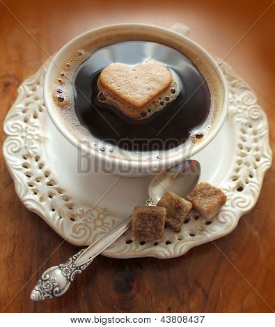 Coffee cup with heart on a wooden table