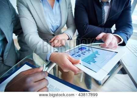 Image of human hands during discussion of business document in touchscreen