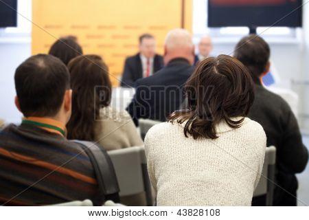 Das Publikum hört das Handeln in einen Konferenzsaal.