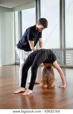 Yoga instructor making adjustment to woman's Bridge Pose at gym