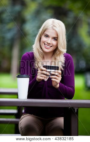 Portrait of happy smiling young woman with cell phone in park
