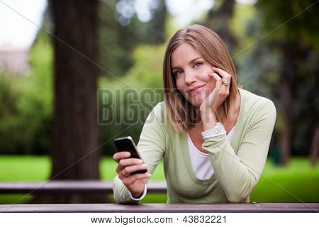 Woman holding Cell Phone in park.