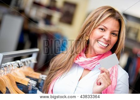Happy woman shopping with a credit card in a retail store