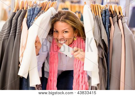 Very happy shopping woman holding a credit card at the store