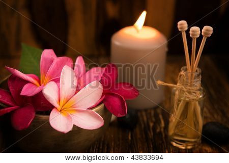 Wellness and spa concept with candles, frangipani flower, sandalwood and rattan sticks on massage table.