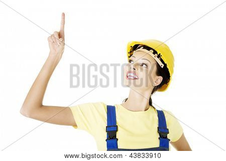 Female construction worker pointing on copy space, isolated on white