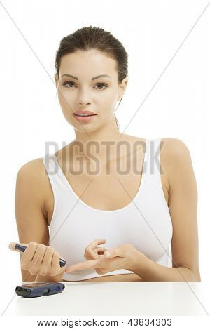 Diabetes patient measuring glucose level blood test using ultra mini glucometer and small drop of blood from finger isolated on a white background