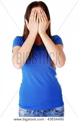 Young teen woman covering her face with hands, isolated on white