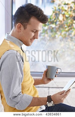 Young businessman sitting at window, drinking coffee, reading newspaper, smiling.
