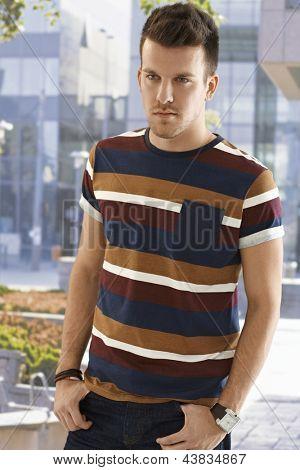 Retrato de jovem casual ao ar livre de pé com as mãos nos bolsos, olhando para longe.