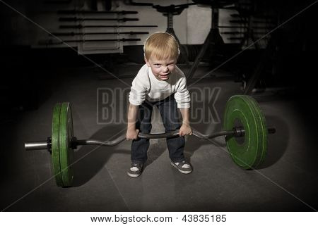 Determined Young Boy trying to lift Heavy weights