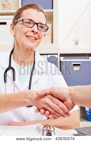 Senior female doctor and patient shaking their hands in office