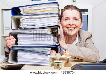 Happy business woman in office with a stack of files