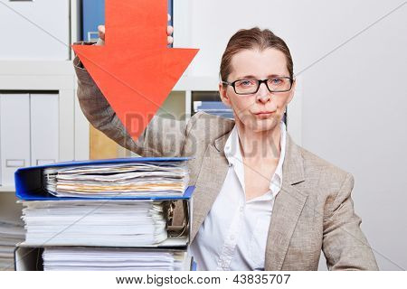 Serious business woman in her office pointing with arrow to many files