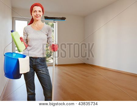 Senior cleaning lady with cleaning products standing in an empty apartment room