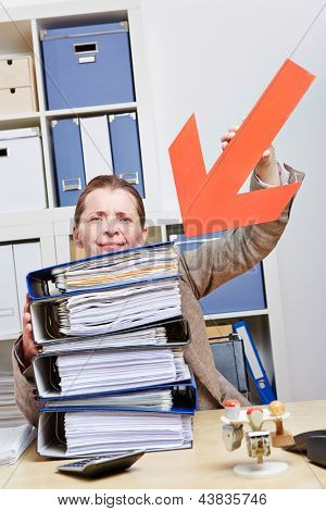 Stressed business woman pointing with arrow to stack of files
