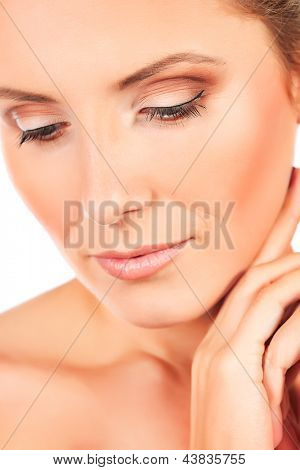 Close-up portrait of a beautiful young woman taking care of her face. Isolated over white background