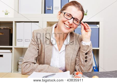 Nearsighted business woman with glasses sitting at her desk in the office