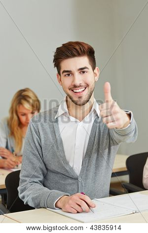 happy young student holding his thumbs up in university class